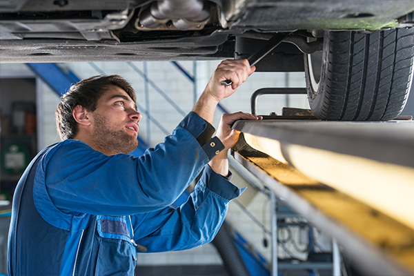 An image of a mechanic working on a cars suspension.